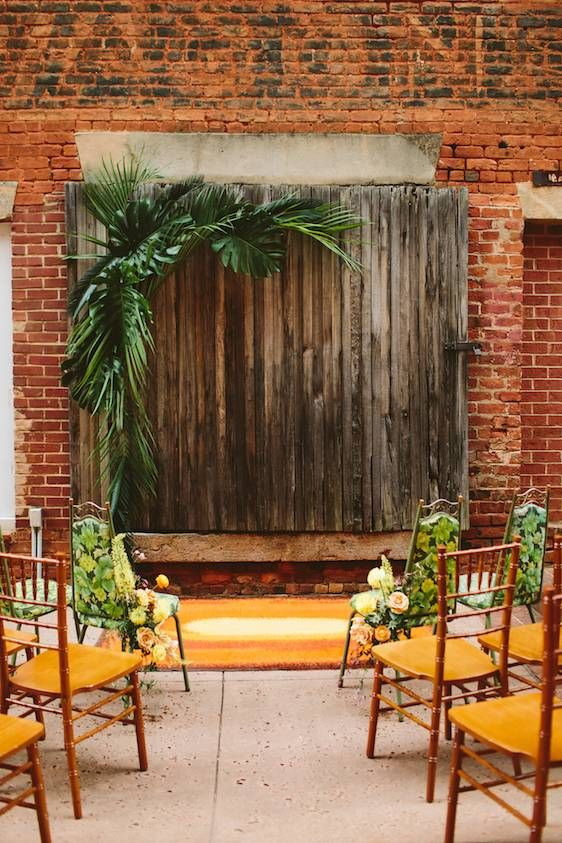 a tropical mid-century modern wedding backdrop of stained wood and tropical leaves is a lovely idea for a modern wedding
