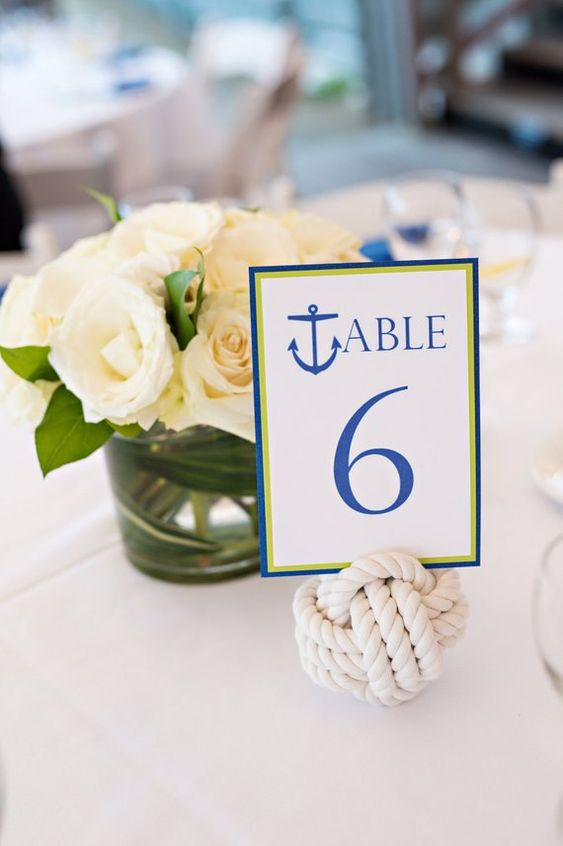 a very simple nautical wedding centerpiece of white roses, a rope ball with a table number is a perfect idea to rock