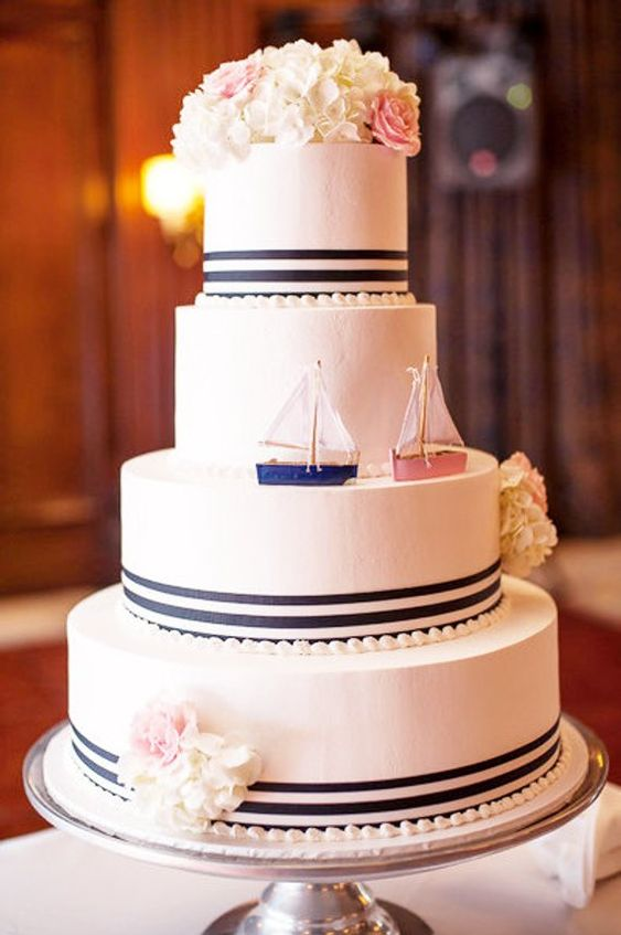 a vintage-inspired nautical wedding cake with navy stripes, pearls, white and pink blooms and two boats instead of a usual topper