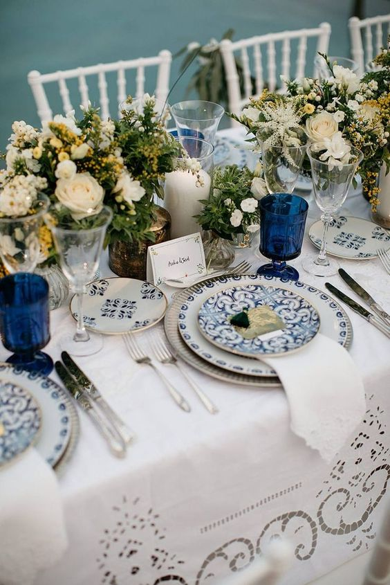 a vintage-inspired nautical wedding tablescape with a crochet tablecloth and napkins, blue patterned plates, neutral blooms and candles