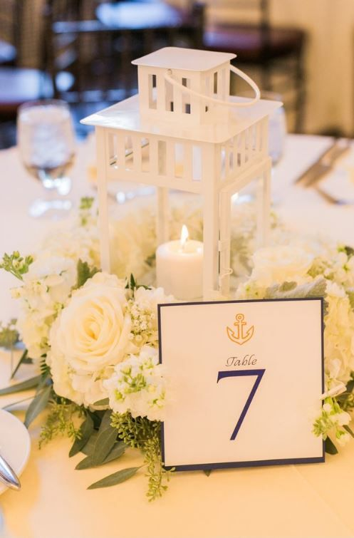 a vintage-inspired wedding centerpiece of white blooms and a candle lantern plus a table number is a chic idea