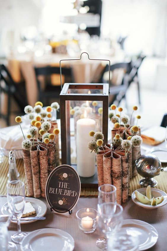 a whimsical fall wedding centerpiece of billy balls, seed pods, a candle lantern and bark vases is a lovely idea
