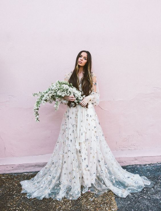 a white A-line wedding gown with a V-neckline, illusion puff sleeves and a layered skirt with a train plus silver foil stars over the dress