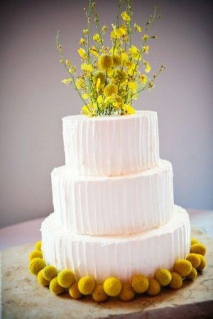a white buttercream wedding cake lined up with billy balls and decorated with billy balls and blooming branches on top