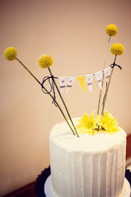 a white buttercream wedding cake with billy balls, a bunting as a topper and yellow blooms is ideal for a rustic wedding