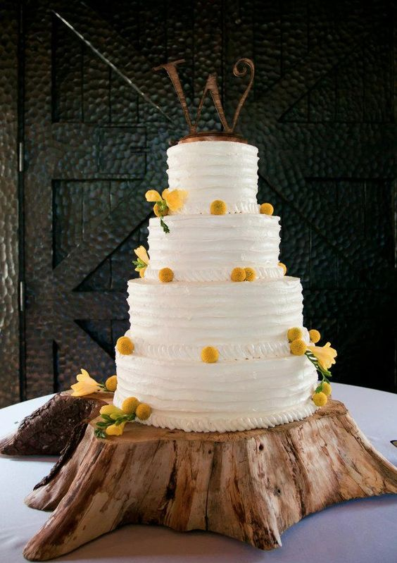 a white buttercream wedding cake with billy balls and yellow blooms plus a metal monogram on top is chic