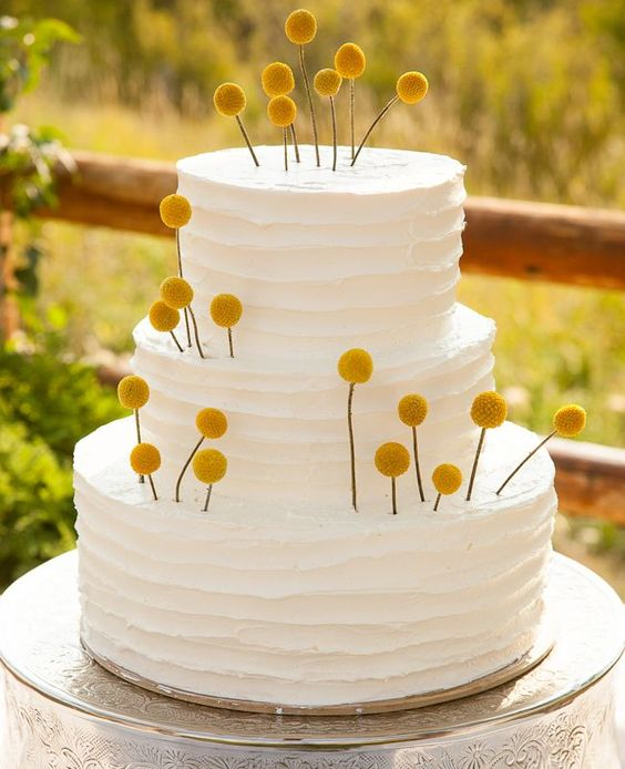 a white buttercream wedding cake with lots of billy balls inserted is a lovely and pretty idea to decorate a cake easily