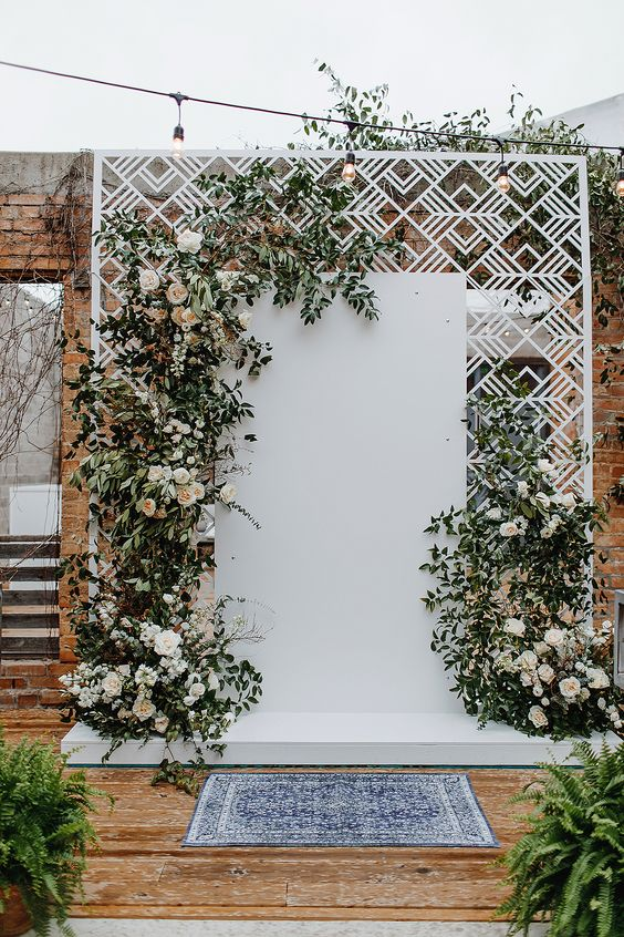 a white laser cut metal backdrop with greenery and white peony roses is a fresh take on a mid-century modern wedding one