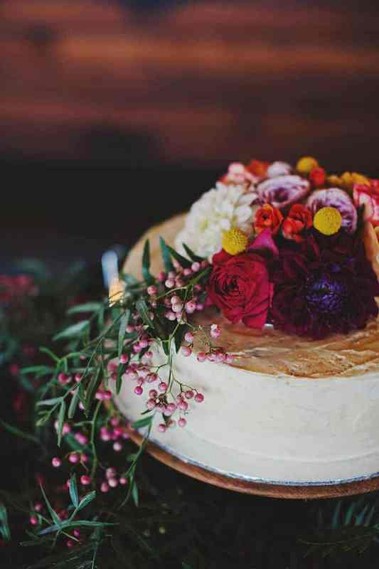 a white one tier wedding cake topped with jewel tone blooms, billy balls and pink berries with greenery