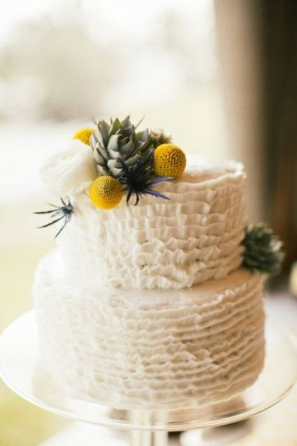 a white ruffle wedding cake with a succulent,a  white peony, thistles, billy balls is a stylish idea for a spring or summer wedding