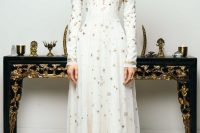 a white sheath wedding dress with a turtleneck, long sleeves, a pleated skirt and gold stars embroidered all over the gown