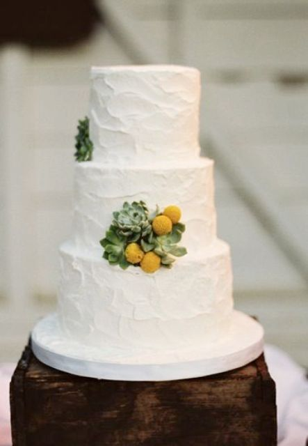 a white textural buttercream wedding cake decorated with a bit of succulents and billy balls is a lovely and stylish option to rock