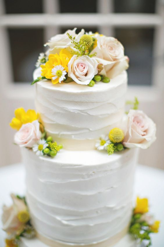 a white textural buttercream wedding cake topped with blush roses, berries, various blooms and billy balls is elegant and cool