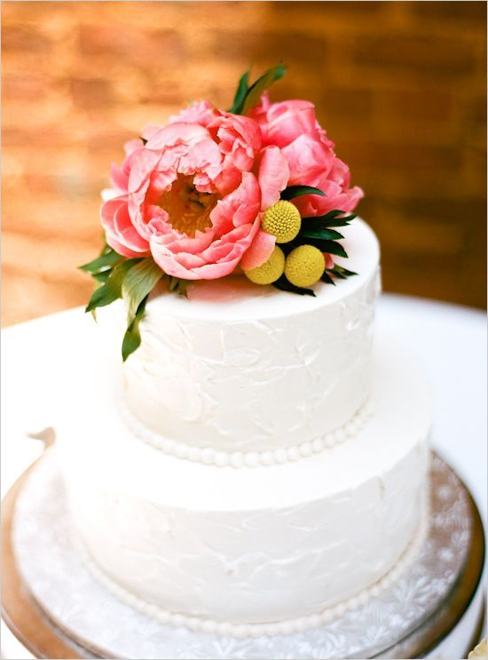 a white textural wedding cake with coral peonies and billy balls is a pretty and stylish idea with plenty of color