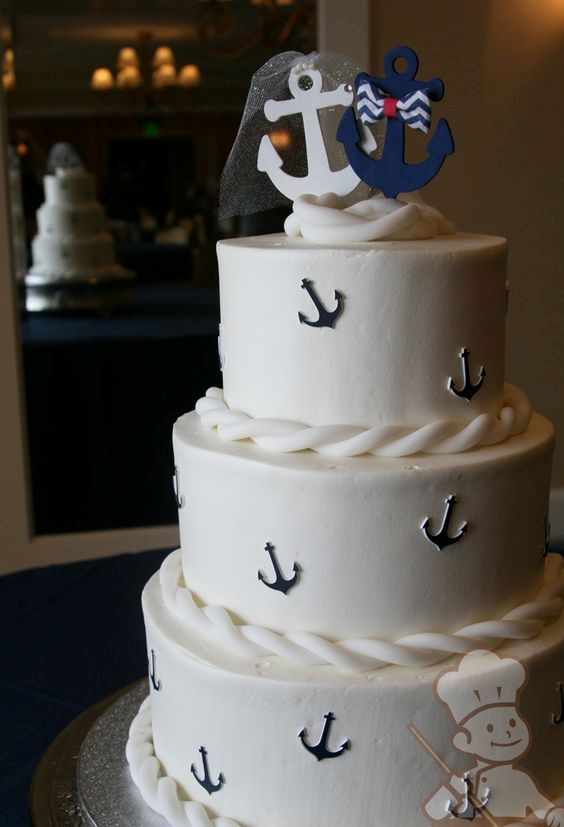 a white wedding cake with ropes, navy anchors, a white and anavy anchor on top, with a veil and a bow is amazing