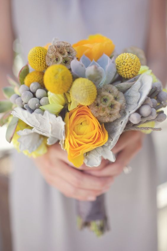 a winter wedding bouquet with pale succulents, berries, seed pods, yellow blooms and billy balls is adorable