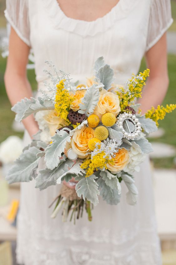 a winter wedding bouquet with yellow roses, billy balls, pale foliage, a pearl brooch is a chic idea