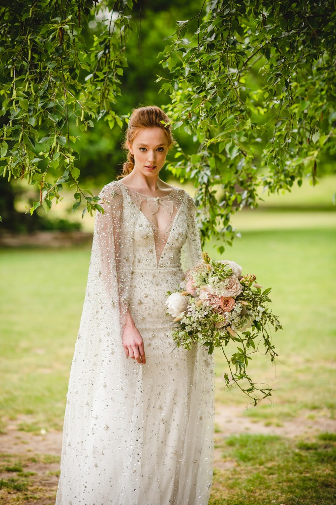 an amazing sheath wedding dress with a covered plunging neckline, a capelet and embellishments all over the dress and capelet