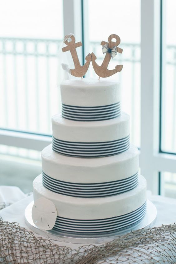 an elegant nautical wedding cake with navy stripes, a seashell, plywood anchors with a bow and a veil is cute and chic