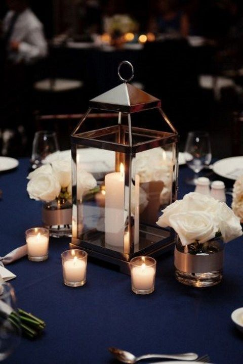 an elegant nautical wedding centerpiece of white roses and candles, a candle lantern is an amazing idea for a nautical wedding