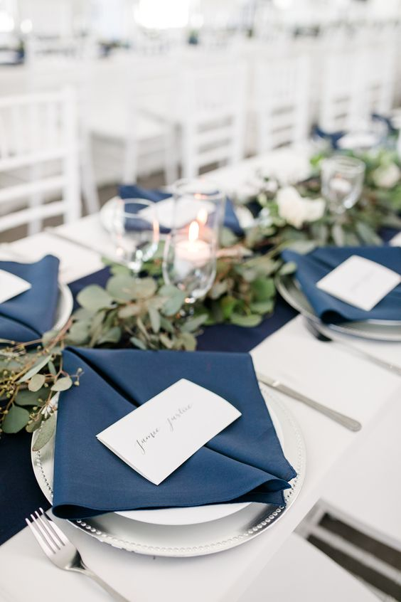 an elegant nautical wedding table setting with a navy runner and napkins, a greenery runner and candles, a silver charger and cutlery