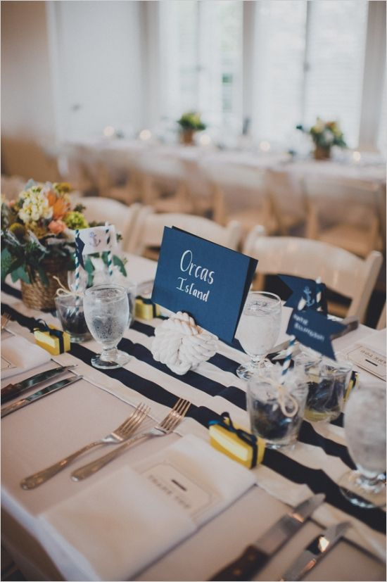 an elegant nautical wedding tablescape with a striped runner, a rope knot stand, pastel blooms and chic cutlery