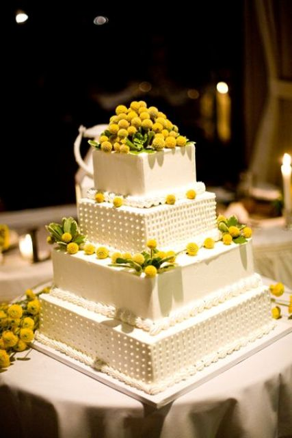 an oversized square wedding cake with lots of billy balls and some foliage is a stylish and refined idea of a wedding dessert