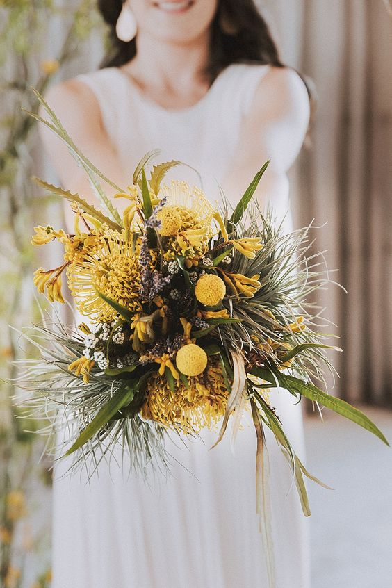 an unusual wedding bouquet of various greenery, yellow blooms and billy balls, astilbe looks textural and very pretty