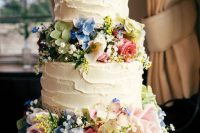 02 a beautiful white buttercream wedding cake decorated with blush, blue and green blooms, baby's breath is a lovely idea for a secret garden wedding