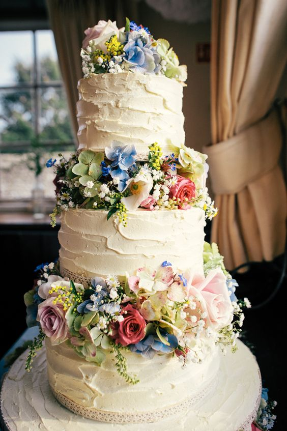 a beautiful white buttercream wedding cake decorated with blush, blue and green blooms, baby's breath is a lovely idea for a secret garden wedding