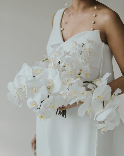 a classic and sophisticated cascading white orchid wedding bouquet is a lovely idea for a refined modern bride or for a tropical one
