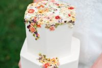 04 a chic hexagon white wedding cake with colorful sugar and pressed blooms and foliage is a gorgeous idea for a secret garden wedding