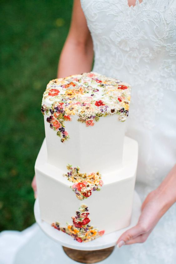 a chic hexagon white wedding cake with colorful sugar and pressed blooms and foliage is a gorgeous idea for a secret garden wedding