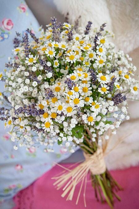 a relaxed summer wedding bouquet of baby's breath, lavender, daisies with a simple wrap is a very cool and fun idea