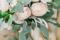 04 a romantic and delicate wedding bouquet with white and blush ranunculus, eucalyptus and white ribbons is chic