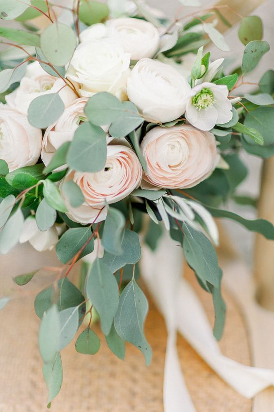 a romantic and delicate wedding bouquet with white and blush ranunculus, eucalyptus and white ribbons is chic