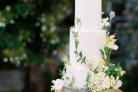 05 a chic secret garden wedding cake in white, with fresh white and yellow blooms and greenery is a lovely idea for a relaxed garden wedding