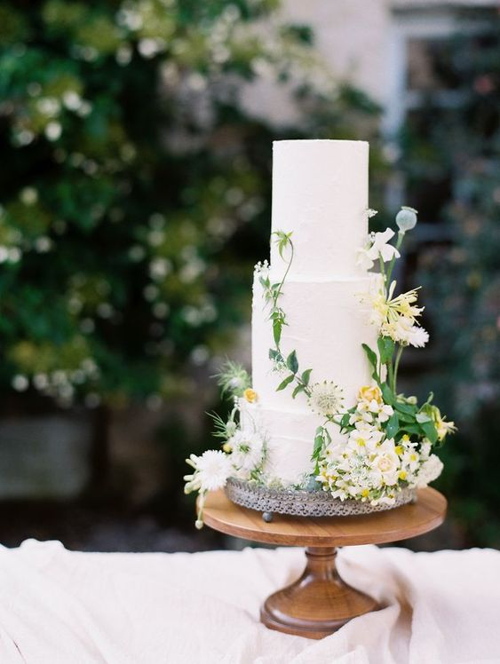 a chic secret garden wedding cake in white, with fresh white and yellow blooms and greenery is a lovely idea for a relaxed garden wedding