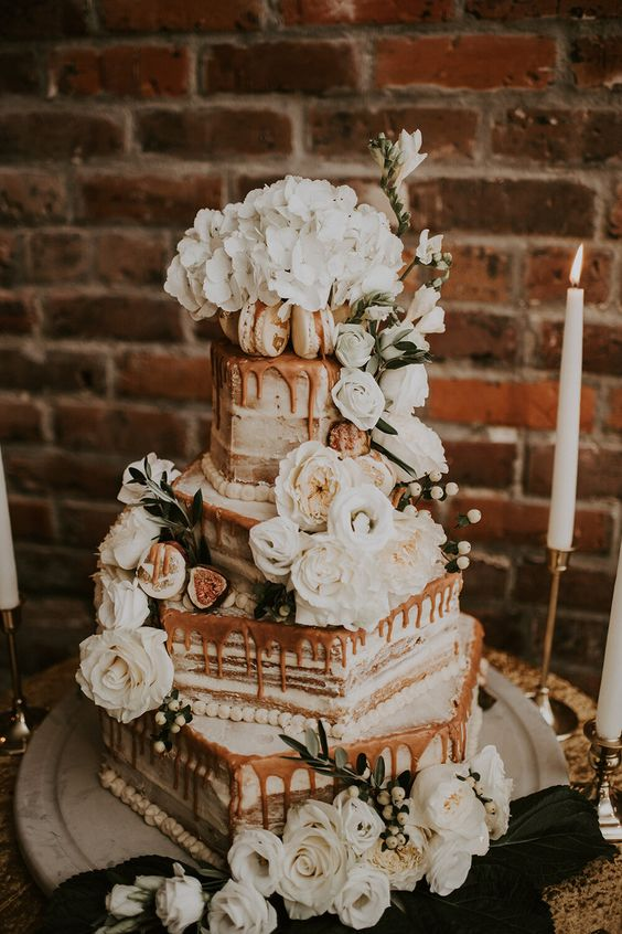 a chic secret garden wedding cake with geometric tiers, white blooms, caramel drip is a fantastic idea for summer or fall
