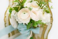 06 a simple and pretty blush ranunculus wedding bouquet with some greenery and blue ribbons is amazing for spring