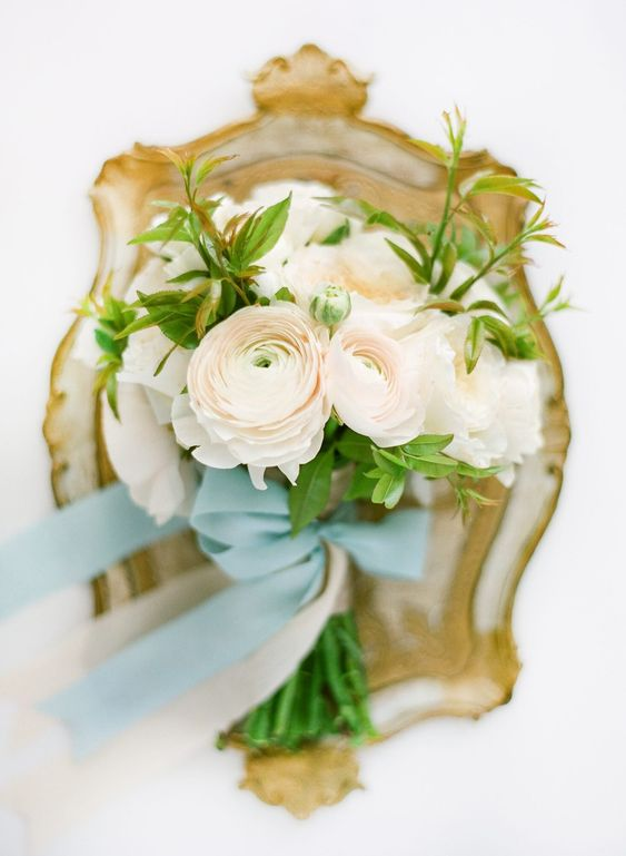 a simple and pretty blush ranunculus wedding bouquet with some greenery and blue ribbons is amazing for spring