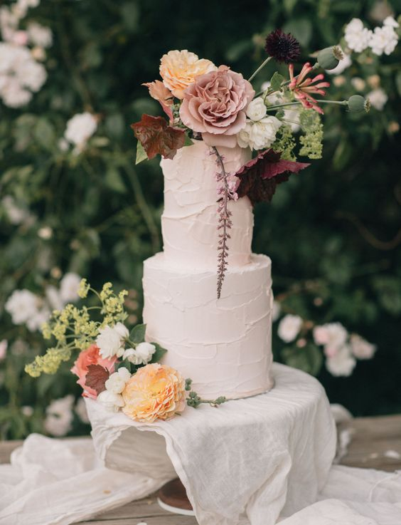 a fabulous secret garden wedding cake with textural buttercream, pastel blooms and greenery on top is a lovely idea