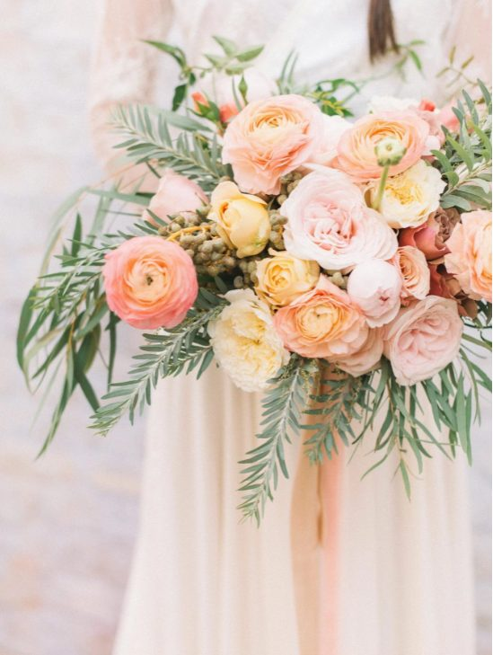 a bright wedding bouquet with pink ranunculus, blush peonies and yellow roses, greenery and berries