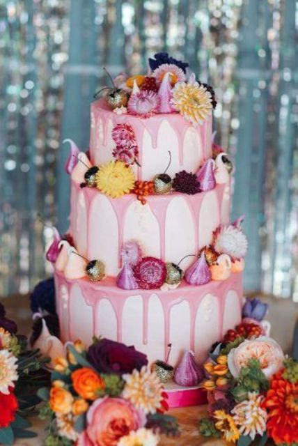 a fabulous wedding cake with pink drip, bright blooms and meringues is a gorgeous idea for a bright summer wedding