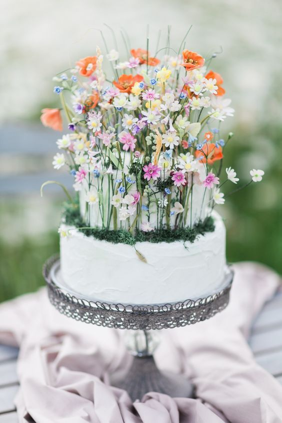 a fantastic wedding cake in white, with tiny colorful flowers, moss and foliage is a lovely idea for a secret garden wedding