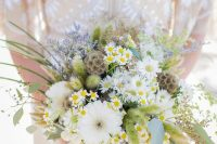 10 a beautiful wedding bouquet with seed pods, daisies, white blooms, greenery and some lavender for a summer bride