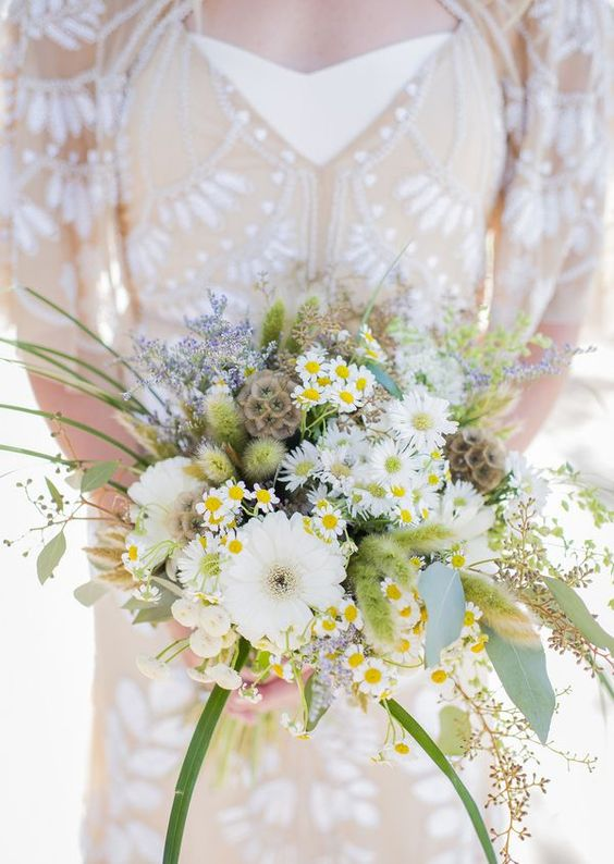 a beautiful wedding bouquet with seed pods, daisies, white blooms, greenery and some lavender for a summer bride