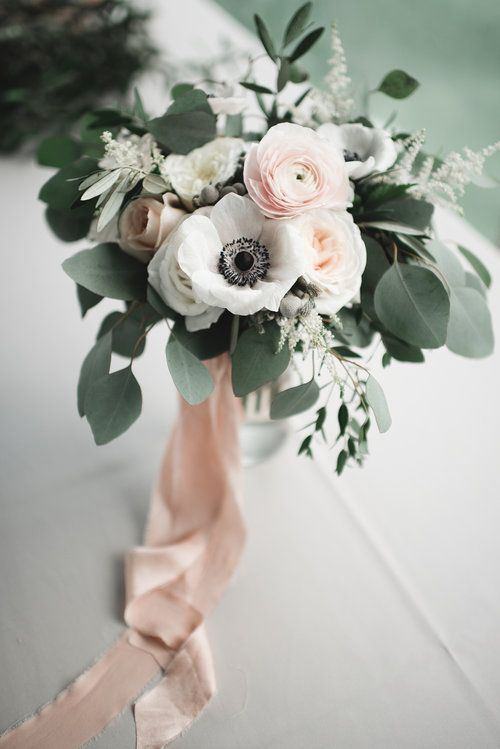 a delicate and romantic wedding bouquet of white and blush ranunculus, white anemones, greenery and foliage plus blush ribbons