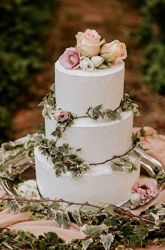 a lovely white buttercream wedding cake decorated with greenery, pink and blush roses is a pretty idea for a secret garden wedding