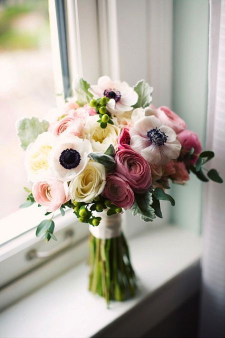 a cool wedding bouquet of pink, bold pink and white ranunculus, white anemones and pale foliage is very romantic